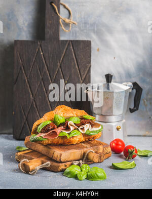 Croissant sandwich with smoked meat Prosciutto di Parma, sun dried tomatoes, fresh spinach and basil on stone textured - Stock Photo