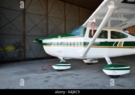 A small plane, parked in hangar airplane. - Stock Photo