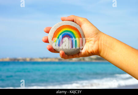 Woman hand holding pebble with painted rainbow against blue sky and sea. - Stock Photo