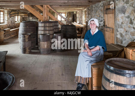 Woman in period costume sitting on barrels in the King's Storehouse at the Fortress of Louisbourg, Louisbourg, Cape - Stock Photo