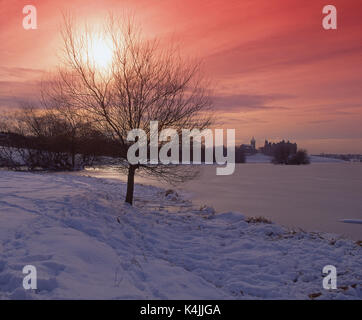 Winter sunset from the frozen shore of Linlithgow Loch with distant Linlithgow Palace, West Lothian - Stock Photo