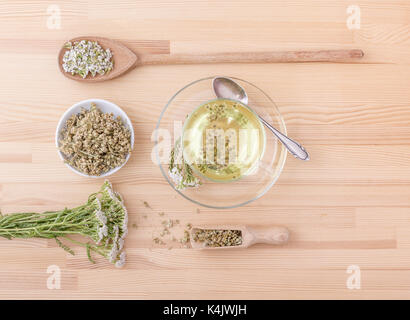 Top view of a Cup with  yarrow tea, fresh and dried yarrow - Stock Photo