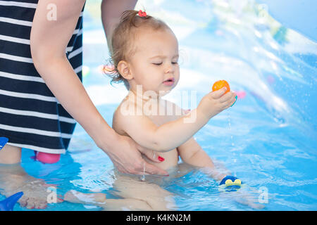 Sixteen months old baby girl playing in the plastic pool with toys - mother standing next to her, keeping an eye - Stock Photo