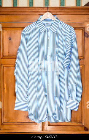 Mans shirt hanging up on a clothes hanger in front of a pine wardrobe, UK. - Stock Photo