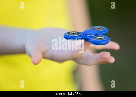 Girl's hand holding a spinning fidget spinner in her hand, spinning them on her index finger - Stock Photo