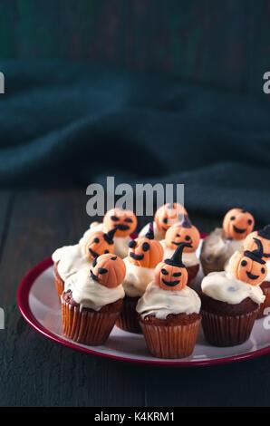 Cupcakes with orange pumpkins - Stock Photo