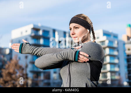 Portrait of a determined young woman stretching her left arm dur - Stock Photo