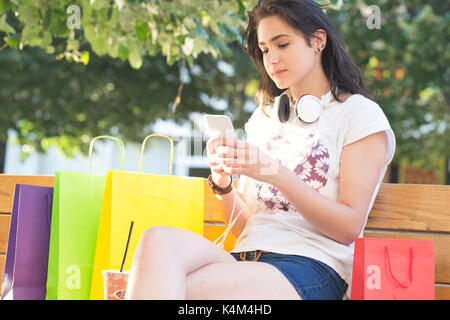 Young beautiful smiling girl, a teenager,with headphones around her neck uses a cell phone and resting on the bench - Stock Photo