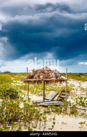 Broken wooden sunloungers and a derelict palm leaf covered parasol on a beach in south Barbuda, Antigua & Barbuda, - Stock Photo