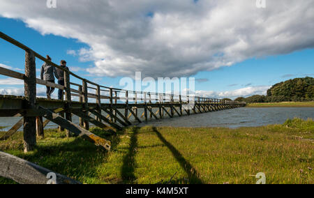 Young couple walking over wooden footbridge over mudflats at high tide, Aberlady Bay local nature reserve, East - Stock Photo