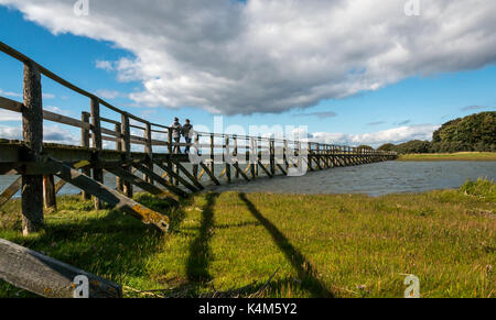 Young couple walking on wooden footbridge over mudflats at high tide, Aberlady Bay local nature reserve, East Lothian, - Stock Photo