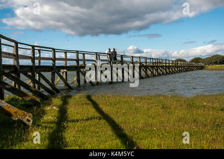 Young couple walking on wooden footbridge over mudflats at high tide at Aberlady Bay local nature reserve, East - Stock Photo