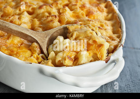High angel view of a dish of fresh baked macaroni and cheese with a wooden spoon over a rustic dark background. - Stock Photo