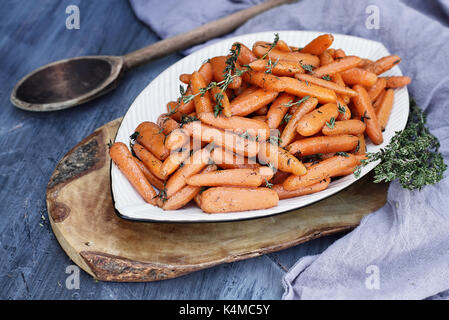 Honey Glazed Baby carrots with an old rustic wooden spoon and thyme. Extreme shallow depth of field with selective - Stock Photo