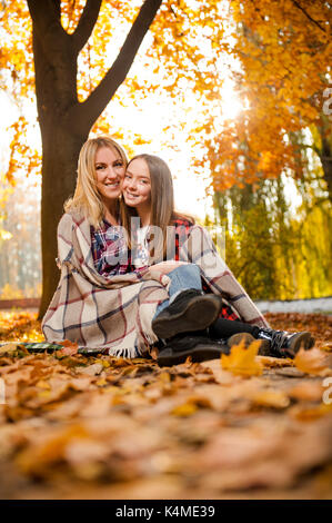 Gorgeous mother hugging her cheerful daughter - Stock Photo