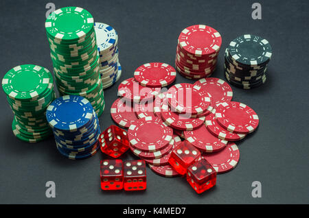 Poker chips stacked on black background and 5 red dice - Stock Photo
