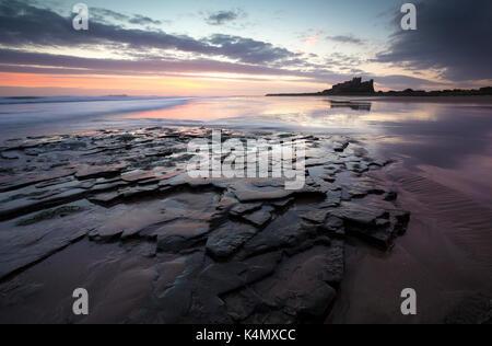 View towards Bamburgh Castle at sunrise from Bamburgh Beach, Bamburgh, Northumberland, England, United Kingdom, - Stock Photo