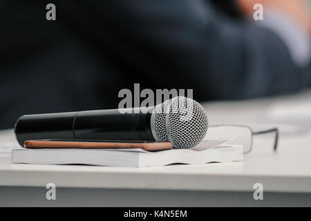 Microphone on table at presentation or business seminar, close up - Stock Photo
