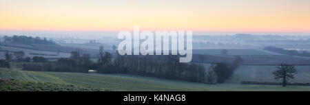 The pink glow of sunrise over a frosted and misty Northamptonshire landscape looking towards Northampton shrouded in mist on the horizon, England.
