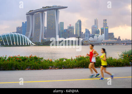 SINGAPORE - FEB 16, 2017: Couple running in Singapore bay at sunset. Motion blur. - Stock Photo