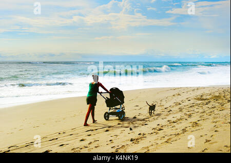Woman with baby carriage and dog walking by the beach. Bali island, Indonesia - Stock Photo