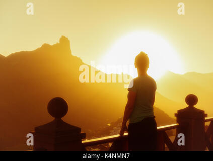 Female hiker looking out over Tejada crater and roque Bentayga from Tejeda village at sunset. Gran Canaria, Canary - Stock Photo