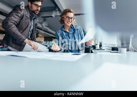 Two architects working on construction plan in office. Happy business partners working together at desk. - Stock Photo