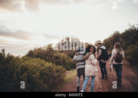 Friends hiking in nature. Group of man and women walking along the countryside road. Woman turning around and looking - Stock Photo