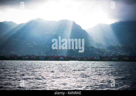 Coastline of Mahe island, Seychelles with sunlight and mountains. View from the boat - Stock Photo
