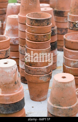 A stack of terracotta pots in the garden. - Stock Photo