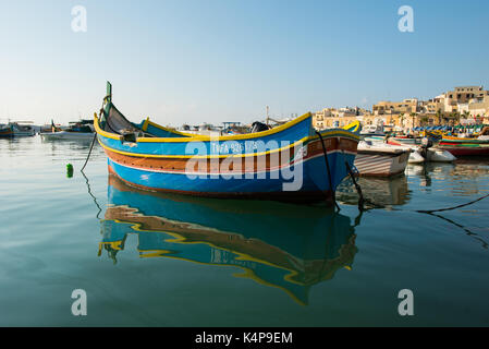 MARSAXLOKK, MALTA - AUGUST 23, 2017: Traditional colorful luzzu fishing boats arriving and anchoring early in the - Stock Photo
