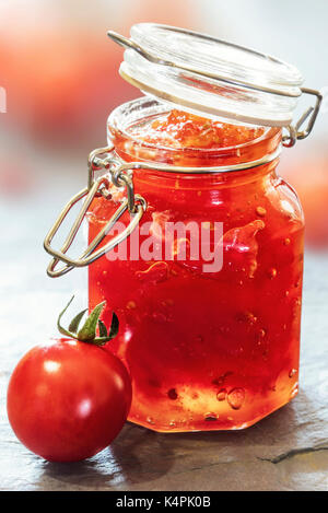 Tomato Jam in a glass jar on a slate table top - Stock Photo