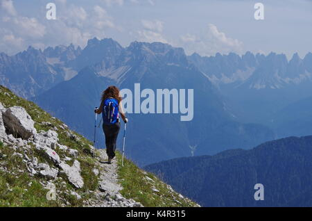 Young femaie trekker hiking on a trail in the Dolomites, Italy, range of Marmarole