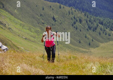 Young femaie trekker hiking on a trail in the Dolomites, Italy, towards the summit of Monte Cavallino on the Austrian border