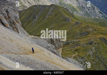 Young femaie trekker hiking on a trail in the Dolomites, Italy