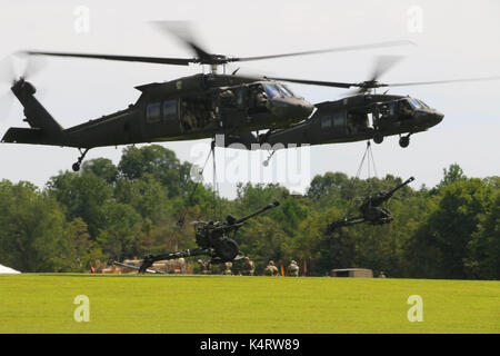 Two UH-60 Black Hawk helicopters of the 101st Combat Aviation Brigade, 101st Airborne Division, sling-load howitzers. - Stock Photo