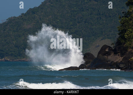 Wave crashing on a rock in Ilhabela, São Paulo, Brazil - Stock Photo