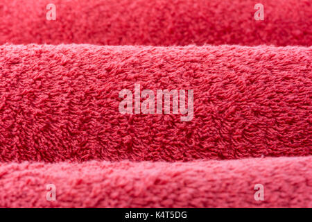 Abstract textures suitable for a background, depicting three rolled up, red terry towelling towels, in close up - Stock Photo