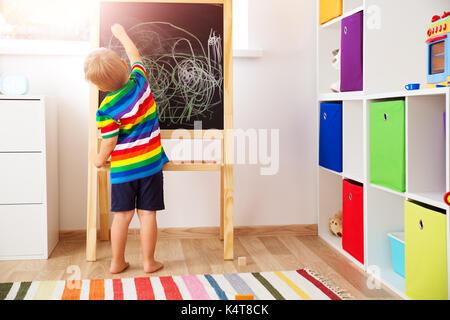 little child drawing on the blackboard - Stock Photo