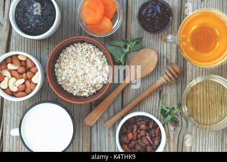 Healthy food. Oat flakes, dried fruits and yogurt, nuts and honey. Concept: proper nutrition. wooden background - Stock Photo