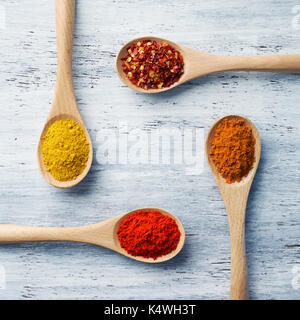 Wooden spoon filled with spices on white painted table - Stock Photo