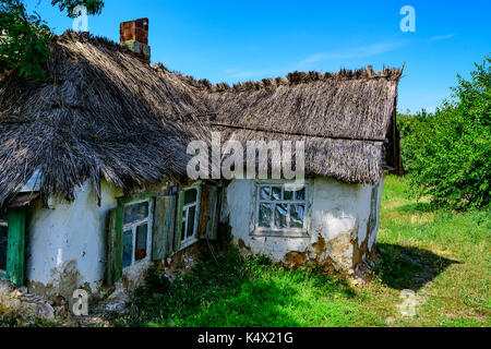 Old rural hut with thatched roof - Stock Photo