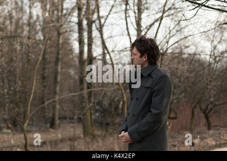 Portrait of a young handsome man sad looking to the left in the park, woods in autumn or spring. Portrait on the - Stock Photo