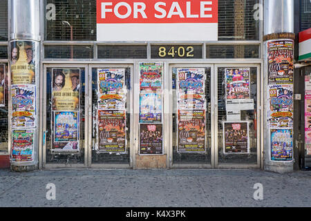 A vacant storefront on Roosevelt Ave. in Jackson Heights, Queens, New York with posters advertising Latin muic shows - Stock Photo