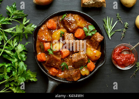 Stewed beef and vegetables in frying pan, top view - Stock Photo