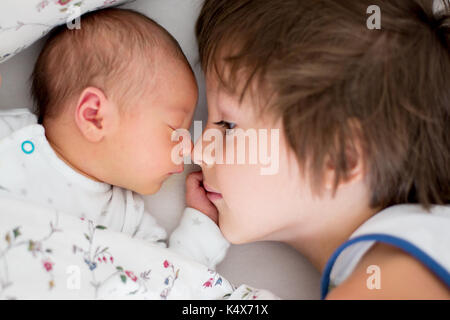 Beautiful boy, hugging with tenderness and care his newborn baby brother at home. Family love happiness concept - Stock Photo