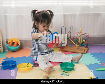 Baby girl play finger paints at home - Stock Photo