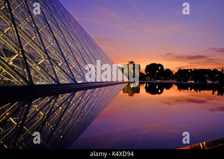 The Louvre in Paris at night as the sun sets - Stock Photo