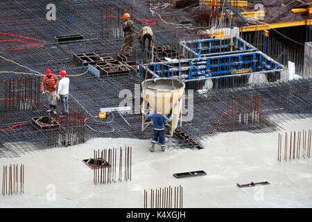 Construction of concrete foundation of new building. Aerial top view of construction site workers leveling cement - Stock Photo