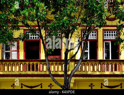 Traditional Singapore shop house exterior with stone balcony windows and wooden louvered shutters in the historic - Stock Photo